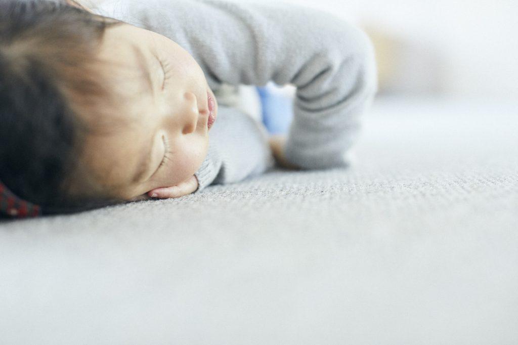 カーペットの上で気持ち良さそうに寝るこども