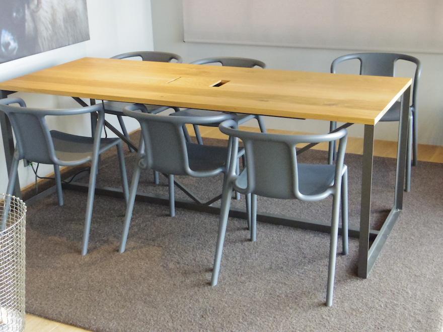 ウールラグの上に重たいテーブルと椅子が6脚乗っている