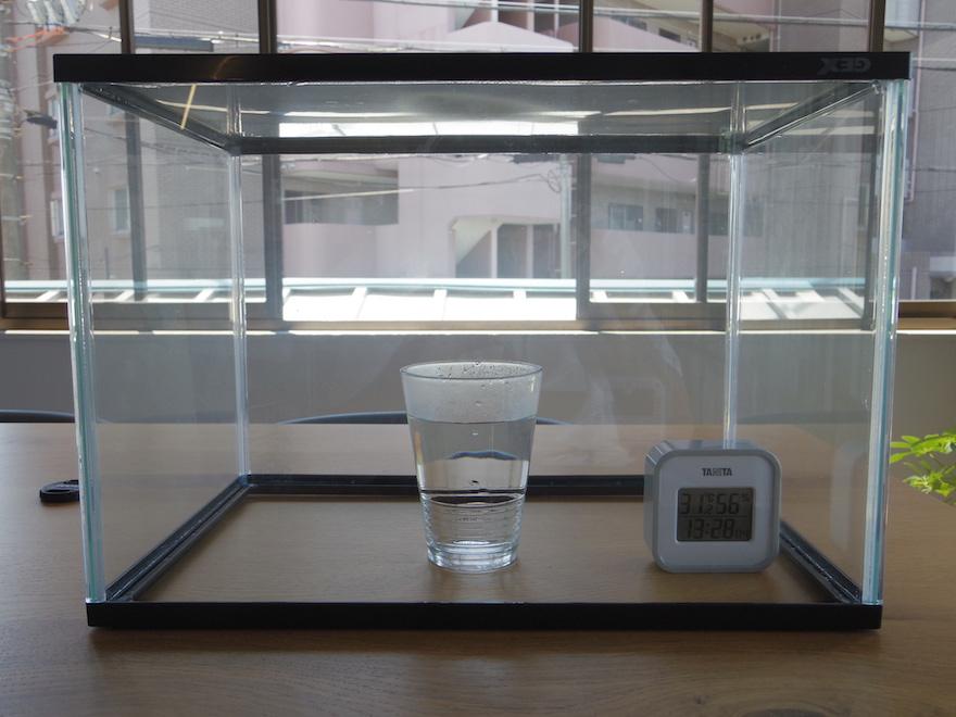 さかさにした水槽の中にお湯を入れたコップと湿度計が入っている
