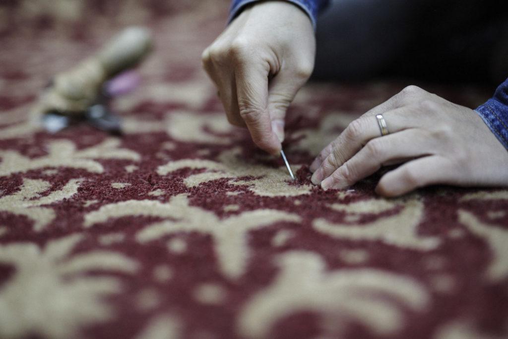 カーペットを針と糸で補修している様子